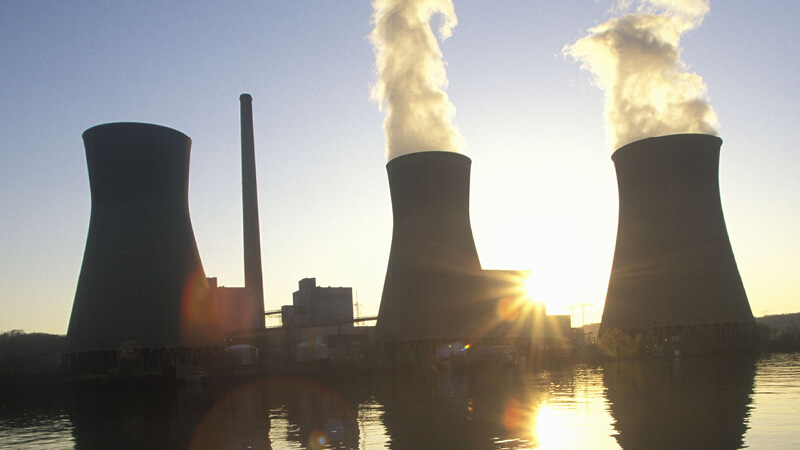 Industrieemissionen eines Kraftwerks vor einer tiefstehenden Sonne