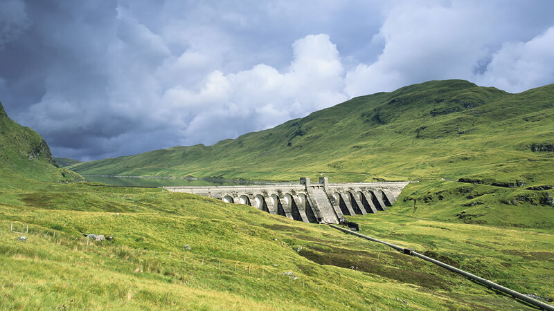 Staudamm zwischen grünen Hügeln