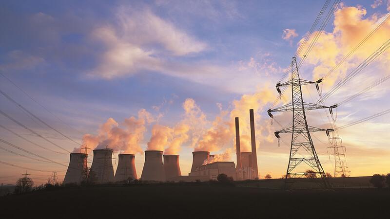 Kraftwerk mit Stromtrasse im Sonnenuntergang