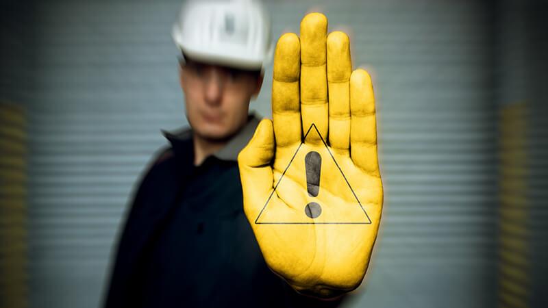 Mann in Sicherheitskleidung streckt seine gelb angemalte Hand mit einem Ex-Schutz Symbol nach vorne