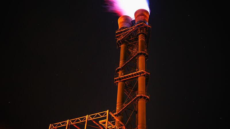 Fackelanlage einer Raffinerie bei Nacht