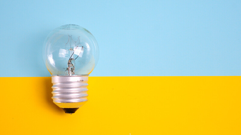 Glühbirne auf blau-gelbem Hintergrund - Symbol zur Ideenfindung