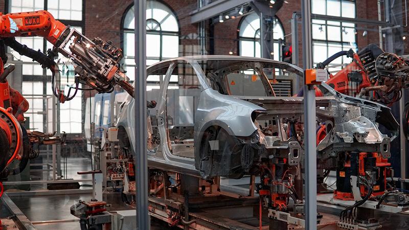 Roboterarme bauen ein Auto in deiner Industriehalle - IT-Sicherheit ist ein wichtiger Baustein