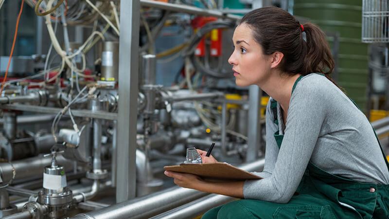 Frau mit Klemmbrett prüft eine technische Anlage