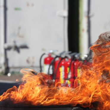 Brandübung mit Übungsfeuer und Feuerlöschern im Hintergrund
