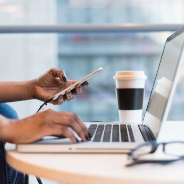 Person sitzt am Laptop und bedient gleichzeitig Smartphone