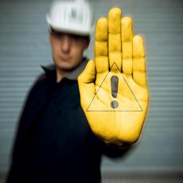 Mann streckt seine Hand als Achtung Gefahr Schild nach vonr
