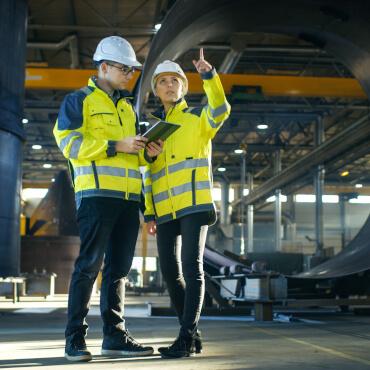 Personen mit Schutzausrüstung in Produktionshalle