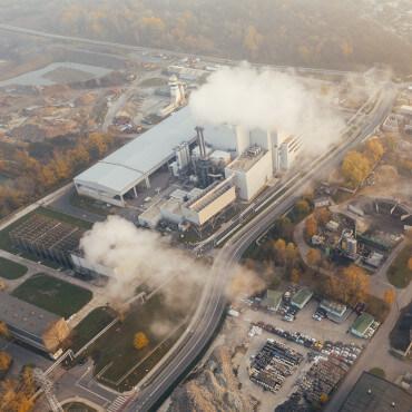 Luftaufnahme einer Industrieanlage mit vielen Rauchabgasen