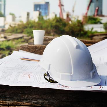 Sicherheitshelm liegt auf Bauzeichnungen