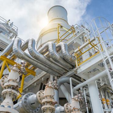 Industrieanlage mit Rohrleitungen und Schornstein