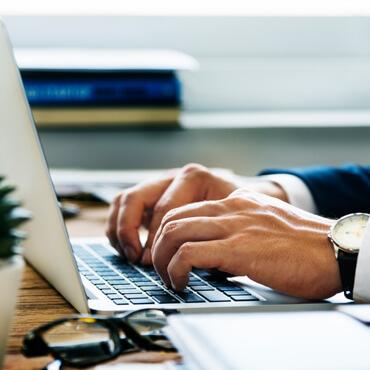 Mann tippt auf Tastatur von Laptop
